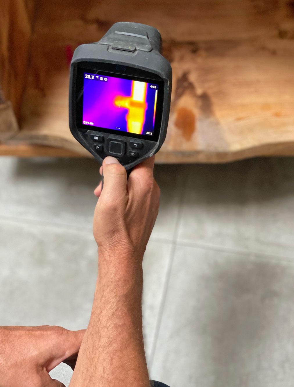 Eine Hand die eine Wärmebildkamera hält, ein verschwommener Hintergrund. Das Bild auf der Kamera zeigt schemenhaft eine gelbe Hand auf einem roten Hintergrund.