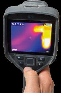 Eine Hand die eine Wärmebildkamera auf einen verschwommen aufgenommen Hintergrund hält. Auf dem Bild der Kamera sind verschwommene Bereiche in Blau, Rot und Gelb zu sehen.