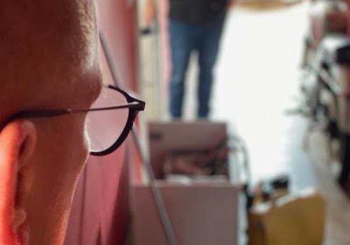 Der Blick auf einen Flur wird hier sichtbar. Links nimmt ein seitlich fotografierter Männerkopf mit Brille und sehr kurzen Haaren circa ein Drittel des Bildes ein, vor ihm sind Kartons, Handwerkerkoffer, viel Chaos und schemenhaft ist ein weiterer Mann zu sehen.