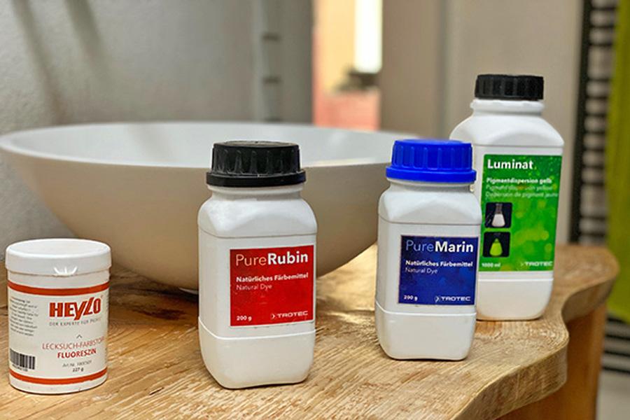 In einem Badezimmer stehen auf dem Waschbeckentisch mehrere weiße, hohe Dosen. Pure Rubin ist jeweils die Aufschrift in unterschiedlichen Farben.