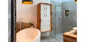 Aufnahme eines Badezimmers, Badewanne, Waschbecken und Badschrank sind weiß, der Boden hat graue Fliesen, schwarze Highlights durch zwei Lampen und eine Heizung, alles in allem wird ein Industrie-Look verkörpert.